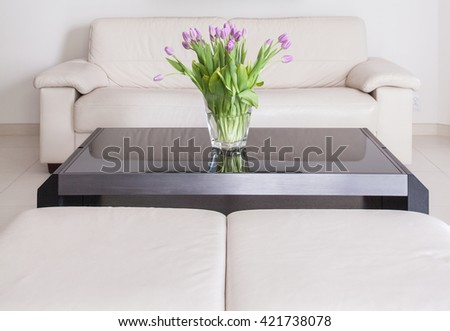 Living room with cream sofa and tulips bouquet