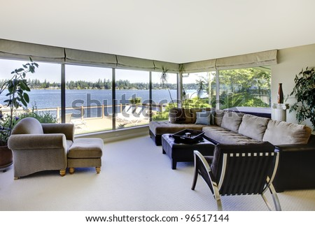Living room with fireplace, modern furniture and water view with large windows. - stock photo