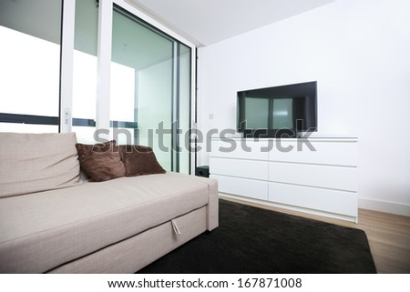 Living room with flat screen television in apartment