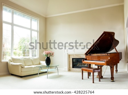 Living room with grand piano, fireplace, sofa and large window with bright daylight coming entering room.