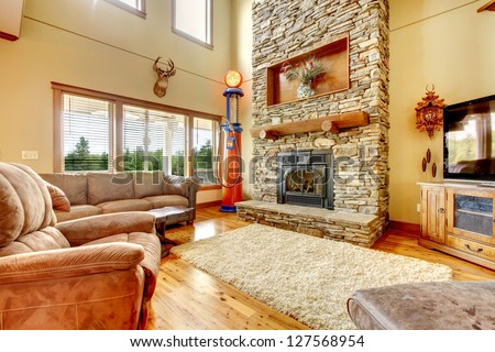 Living room with high ceiling, stone fireplace and leather sofa. - stock photo