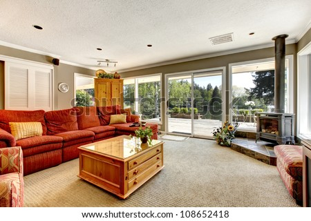 Living room with many windows, red sofa and stove. - stock photo