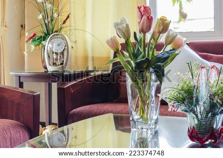 living room with red fabric sofa and flower in glass vase