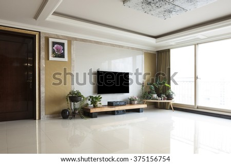 Living room with smart television(TV, LED, LCD, HD, Full HD, UHD, display), gold wall, white marble stone, wood table, audio, green plant pot, flower pot, picture.