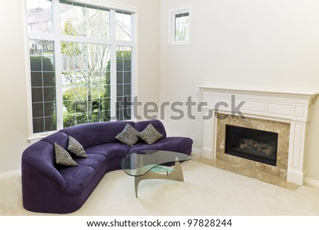 Living room with sofa, glass table, fireplace and carpet floors with large window in background - stock photo
