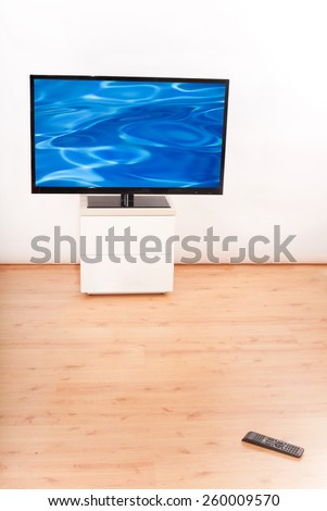 Living room with TV and a remote control on the floor - stock photo