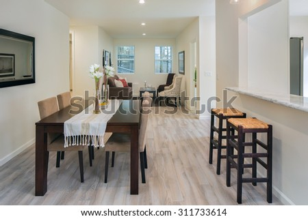 Living room with wooden floor and dining table and bar chairs. - stock photo