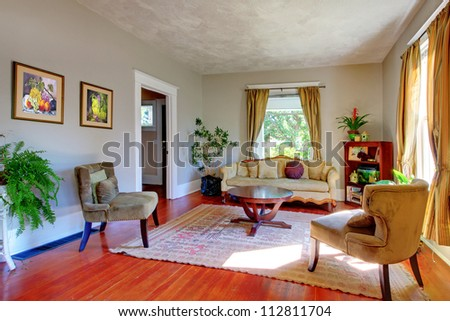 Living room with yellow curtains, grey walls and antique sofas. - stock photo