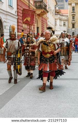 LJUBLJANA, SLOVENIA - AUGUST 24th 2014: Column of ancient Roman legionnaires walking on the streets of Ljubljana on a summer afternoon.  - stock photo
