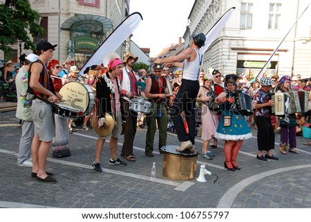 LJUBLJANA, SLOVENIA - JULY 1: Belgian brass band De Propere Fanfare Van De Vieze Gasten at traditional street theater festival Ana Desetnica on July 1, 2012 in Ljubljana, SI. Band in gaudy dresses.