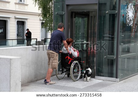 LJUBLJANA, SLOVENIA -  JUNE 28, 2014: Husband and wife in a wheelchair with a dog come in passenger lift. LJUBLJANA, JUNE 28, 2014 - stock photo