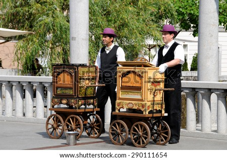 LJUBLJANA, SLOVENIA - JUNE 13, 2015: Slovenian Barrel organ players try to evoke nostalgic atmosphere on Cobblers bridge in old city center   - stock photo
