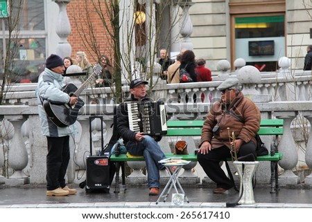 LJUBLJANA, SLOVENIA-MAR. 27, 2015:  Street musicians perform on Preseren Square in Old Town Ljubljana before passing pedestrians.  Musicians are found on every street in old town in good weather. - stock photo