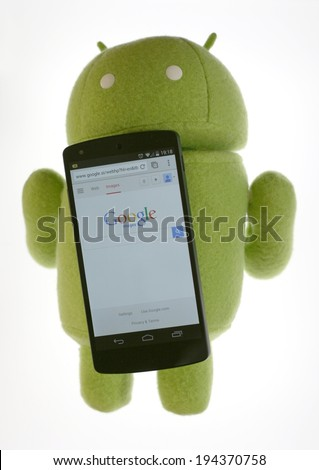 LJUBLJANA, SLOVENIA - MAY 21, 2014: Google Nexus 5 LG smartphone with Android robot figure plush toy. The Nexus 5 is the first device to feature version 4.4 of Android operating system. - stock photo