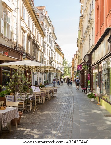 LJUBLJANA, SLOVENIA - 26TH MAY 2016: A view along streets of Ljubljana during the day. Buildings, shops and restaurants can be seen. - stock photo