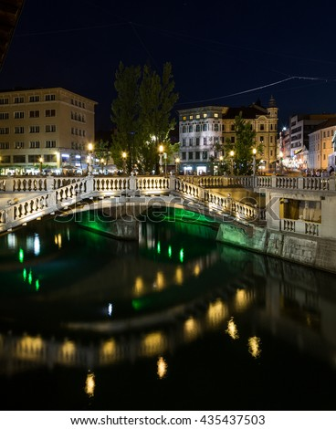 LJUBLJANA, SLOVENIA - 26TH MAY 2016: Part of the Triple Bridges and other buildings in Ljubljana at night. People can be seen.