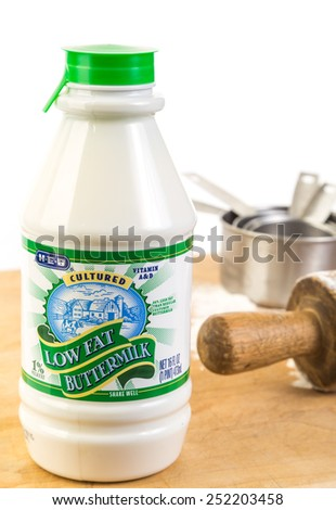 LLANO, TEXAS-FEB 12, 2015: Bottle of buttermilk on wooden cutting board sprinkled with flour.  Also vintage rolling pin and measuring cups. - stock photo