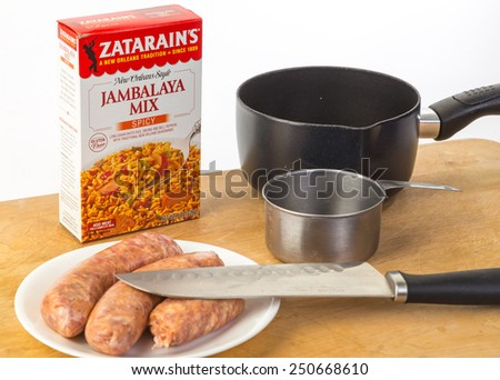 LLANO, TEXAS-FEB 06, 2015: Zatarain's New Orleans Style Jambalaya Mix in a box ready for sauce pan and measured amount of water.   Add Sausage and Eat.  Kitchen utensils against white background. - stock photo