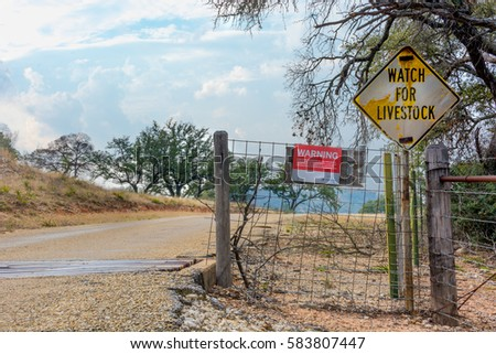 Llano, Texas - February 19 2017: A sign provided by the Texas Farm Bureau states liability law for participants engaged in agritourism activities next to a watch for livestock sign.