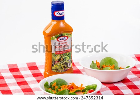 LLANO, TEXAS-JAN 20:  Bottle of creamy Kraft French Dressing on white background with spinach salad on red plaid tablecloth awaiting the dressing. - stock photo