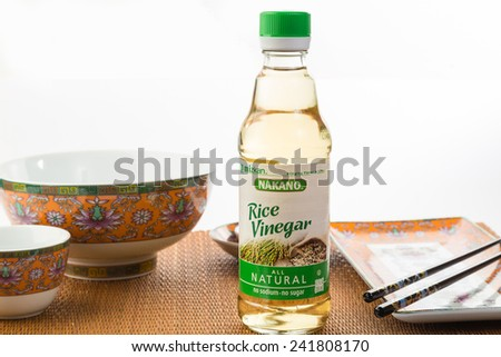 LLANO, TEXAS-Jan 05, 2015:   Bottle of Nakano Rice Vinegar on Bamboo place mat with Oriental Design Dishes as background. - stock photo