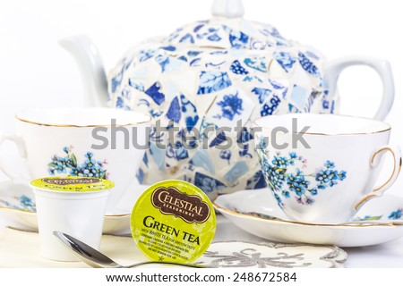 LLANO, TEXAS-JAN 31, 2015:   Green Tea by Celestial Seasonings in K-Cups for Keurig Brewers.  Blue and white teapot and two elegant cups with floral patterns.  Selective focus and copy space. - stock photo