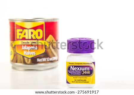 LLANO, TEXAS-MAY 5, 2015:  Selective focus on bottle of Nexium, the Purple Pill, juxtaposed in front of out of focus can of jalapeno peppers to indicate heartburn relief