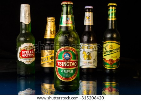 LLANO, TX-SEP 9, 2015:  Condensation drops on cold bottle of Tsingtao Beer imported from China.  Beers of other countries in background. - stock photo