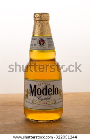 LLANO, TX-SEPT 29, 2015: Condensation dripping from cold bottle of Modelo Especial Mexican Beer.  Golden glow from backlight. Vertical format on white background with copy space. - stock photo