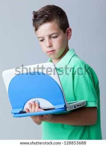 Llittle boy with laptop against grey background - stock photo