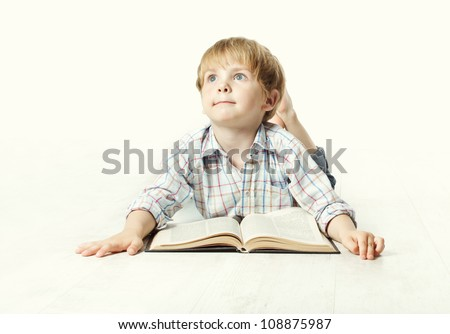 Llittle child reading book  lying down on floor and dreaming