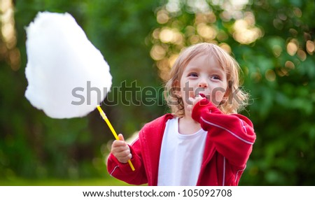 Llittle girl eating cotton candy in the park in spring - stock photo