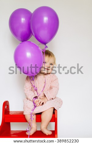 llittle girl sitting on the bench with pink balloon - stock photo
