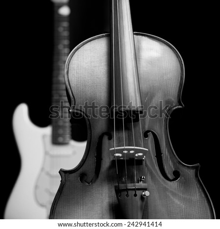 lo-key image of vintage classical violin & electric guitar , isolated on black - stock photo
