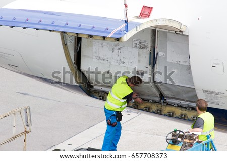 Load of luggage containers in the aircraft cargo compartment. Technicians check the correctness of containers fixing.