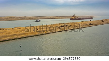 Loaded Bulk carrier passing through Suez Canal with ship's convoy at early morning.