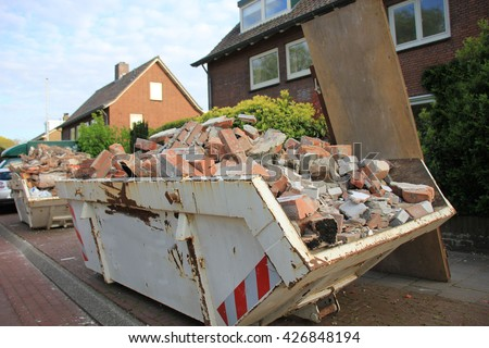 Loaded dumpster near a construction site, home renovation - stock photo