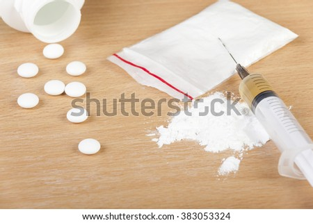 Loaded syringe laying on a bag of heroin and some spilled pills on a table - stock photo