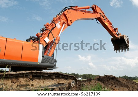 Loader Excavator doing construction works standing in field with risen bucket outdoors