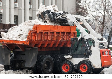 loader pours the snow into the truck on the street - stock photo
