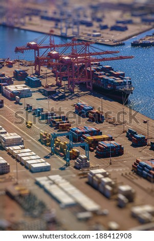 Loading a transport ship with cargo, containers, with tilt-shift lens effect from bird's eye perspective - stock photo