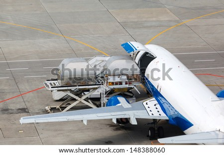 loading and unloading of containers in the cargo aircraft with platform - stock photo