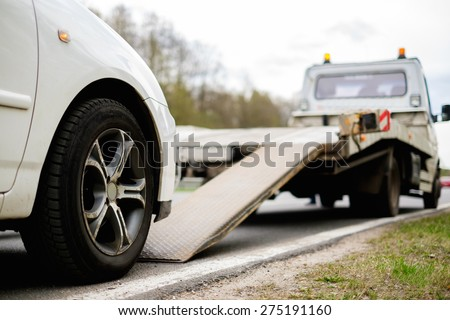Loading broken car on a tow truck on a roadside  - stock photo