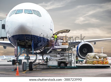 Loading cargo on plane in airport before flight - stock photo