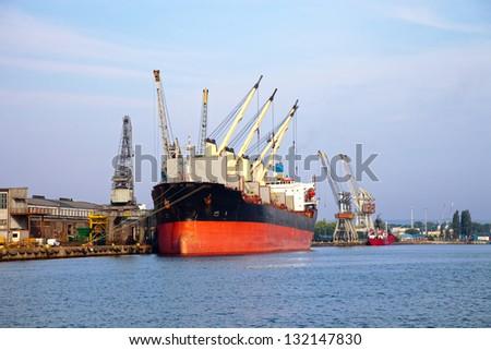 Loading cargo ship in port Gdansk, Poland. - stock photo