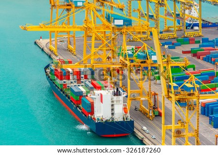 Loading containers on a sea cargo ship, view of the cargo port and container terminal of Barcelona with the Montjuic hill, Barcelona, Catalonia, Spain. - stock photo