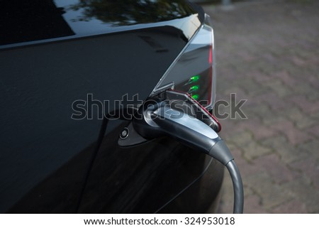 Loading energy of an electric black car - stock photo