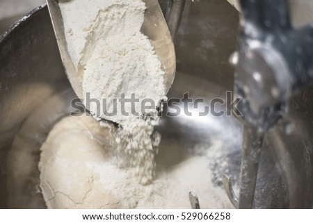 Loading flour into an industrial bakery dough mixer. Close up view.