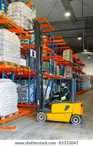 Loading goods with forklift in distribution warehouse - stock photo