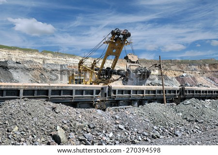 Loading of iron ore on the train - stock photo
